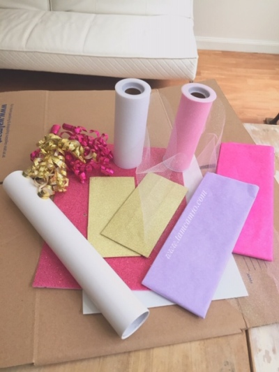 Pink & Purple Tissue paper, Pink & Gold Curling Ribbon, Pink and White Tulle, White Vinyl, Gold Gift Bags, White and Pink foam board and an unfolded cardboard box all from walmart
