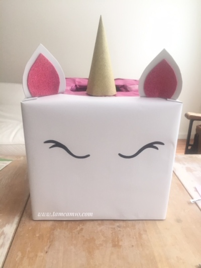 White box with Unicorn horn, ears and eyes.
